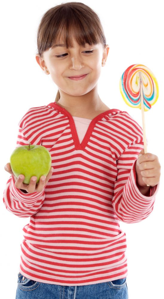 little girl holding apple & lollipop